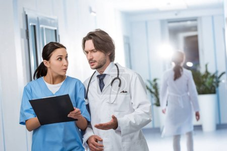 Photo for Concentrated doctor discussing diagnosis with nurse in clinic - Royalty Free Image