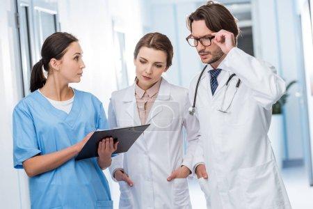 Photo for Doctors discussing diagnosis with nurse in clinic - Royalty Free Image