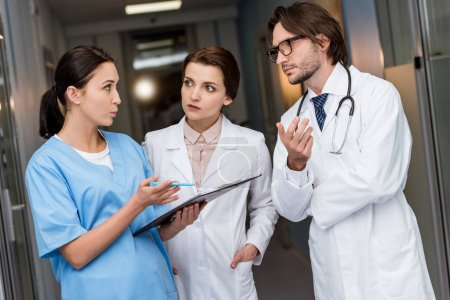Photo for Doctors and nurse with clipboard discussing diagnosis - Royalty Free Image