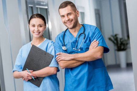 Médicos sonrientes en uniforme azul sosteniendo estetoscopio y portapapeles