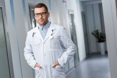 Photo for Doctor in glasses and white coat standing with hands in pockets - Royalty Free Image