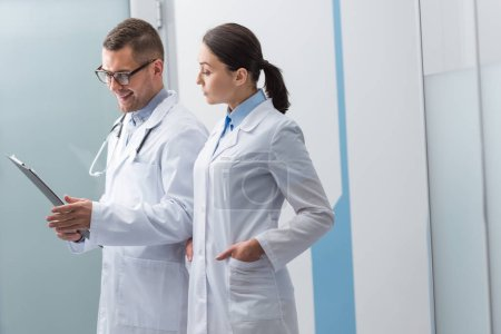 Photo for Doctors in white coats with clipboard discussing diagnosis - Royalty Free Image