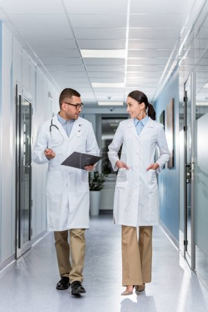 Photo for Doctors in white coats talking and looking at each other - Royalty Free Image