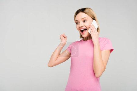Photo pour Excité belle femme en t-shirt rose parlant sur smartphone, isolé sur gris - image libre de droit