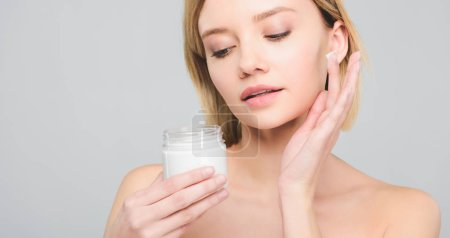 Photo for Tender girl applying cosmetic cream on face and holding plastic container isolated on grey - Royalty Free Image