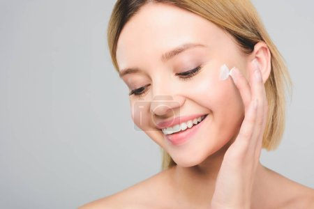Photo for Beautiful smiling young woman applying cosmetic cream on face isolated on grey - Royalty Free Image