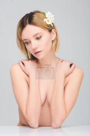 Photo pour Femme nue tendre posant avec des fleurs freesia dans les cheveux, isolé sur gris - image libre de droit