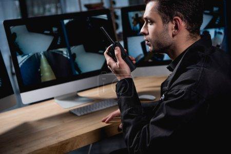 Photo pour Beau garde en uniforme tenant walkie-talkie et écran d'ordinateur en regardant - image libre de droit