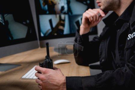Photo pour Vue recadrée de garde dans une tenue uniforme talkie-walkie - image libre de droit