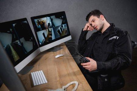 Photo pour Garde ennuyé en uniforme tenant talkie-walkie et regardant le moniteur d'ordinateur - image libre de droit