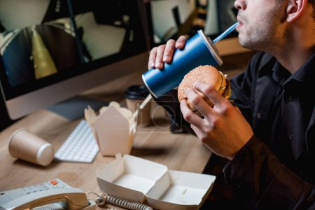 Photo for Cropped view of guard drinking and holding burger at workspace - Royalty Free Image
