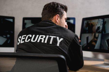 Photo pour Vue arrière du garde en uniforme noir regardant de moniteur d'ordinateur - image libre de droit