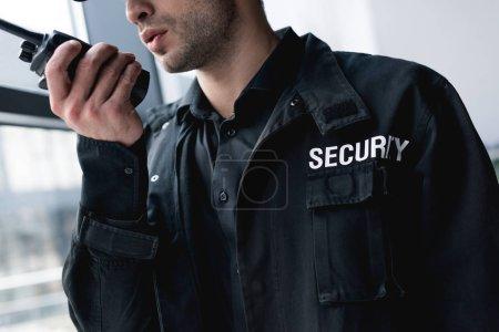 cropped view of guard in uniform talking on walkie-talkie