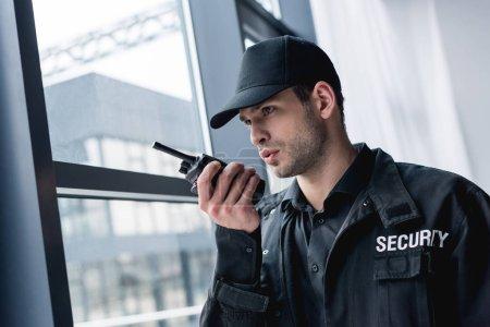 Photo pour Recadrée vue de garde dans uniforme de parler à radio portative et de recherche. - image libre de droit
