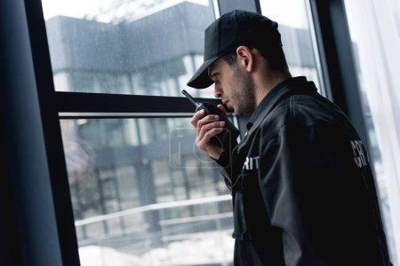 Photo pour Beau garde en uniforme noir parler talkie-walkie - image libre de droit