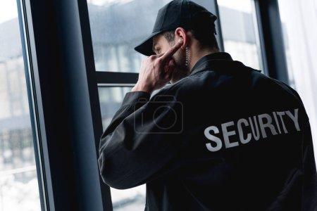 rear view of guard in uniform using earphone