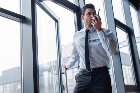 Photo pour Beau garde en costume parlant sur talkie-walkie - image libre de droit