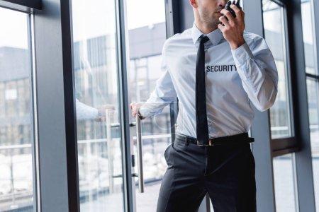 Photo pour Vue recadrée de beau garde en costume parlant sur talkie-walkie - image libre de droit