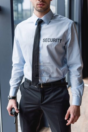 partial view of handsome guard in suit holding walkie-talkie