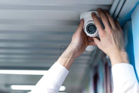 Photo pour Vue partielle de l'homme mise en place de caméra de sécurité - image libre de droit