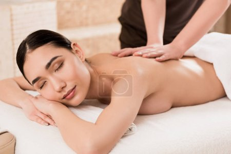 Photo for Cropped view of masseur doing back massage to beautiful asian woman - Royalty Free Image