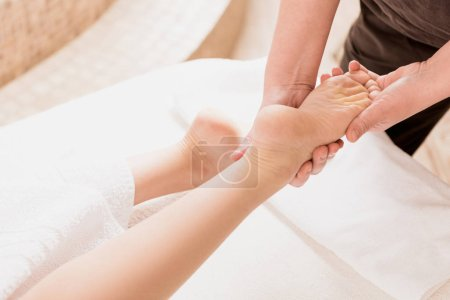 Photo for Partial view of masseur doing foot massage to woman at spa - Royalty Free Image