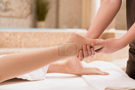 Photo pour Vue recadrée du masseur fait de massage des pieds pour femme - image libre de droit