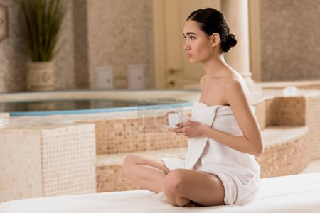 Photo for Beautiful asian woman in towel sitting with coffee cup at spa - Royalty Free Image
