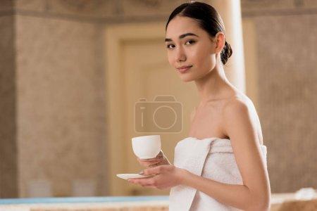 Photo pour Belle asiatique femme en serviette assis avec tasse de café et en regardant caméra - image libre de droit