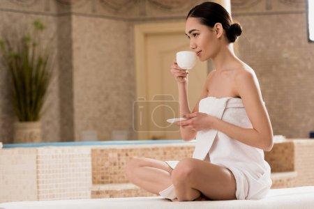 Photo pour Belle femme asiatique éponge boire du café au spa - image libre de droit