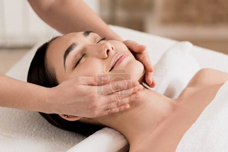 Photo for Woman getting face massage with closed eyes at spa - Royalty Free Image