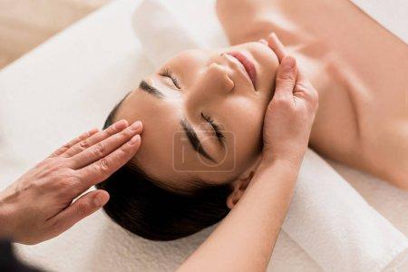 Photo pour Jolie femme asiatique pour massage du visage avec des yeux fermés au spa - image libre de droit