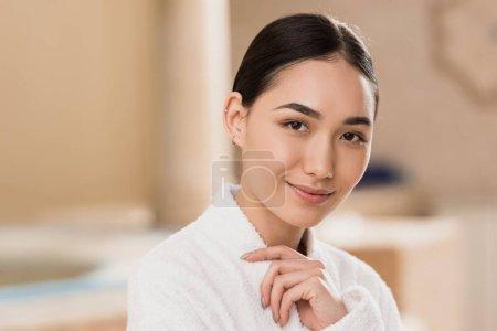 Photo pour Attrayant asiatique femme en peignoir regardant caméra à spa - image libre de droit