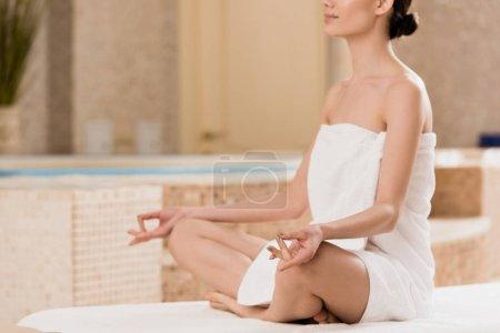 Photo pour Vue recadrée de femme en serviette méditant au spa - image libre de droit