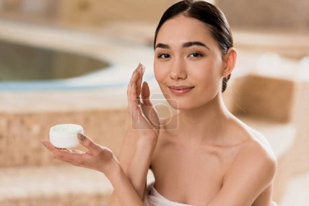 Photo for Beautiful asian woman applying cosmetic cream and looking at camera - Royalty Free Image