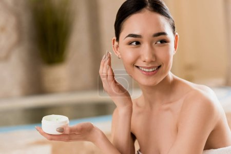 Photo for Attractive asian woman applying cosmetic cream at spa with copy space - Royalty Free Image