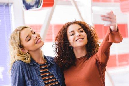 Photo pour Mise au point sélective de sourire et de jolies femmes prenant selfie smartphone au café - image libre de droit