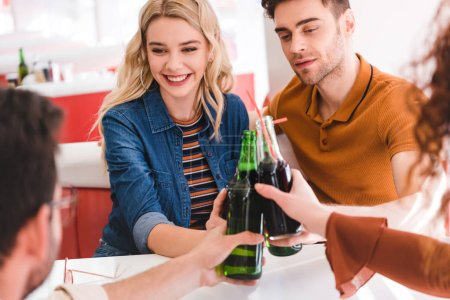 Photo for Selective focus of smiling and attractive friends cheering with soda and beer at cafe - Royalty Free Image