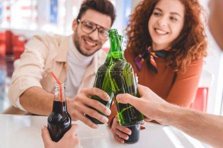 Foto de Enfoque selectivo de botellas de vidrio con bebida por amigos - Imagen libre de derechos