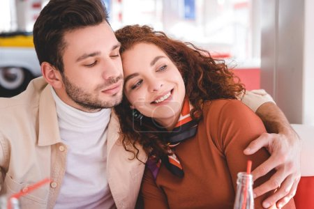 Photo for Beautiful couple hugging, smiling, looking away at cafe - Royalty Free Image
