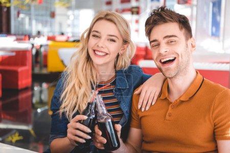 Photo pour Beau couple souriant, regardant la caméra et acclamant avec des bouteilles en verre au café - image libre de droit