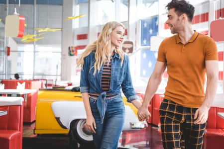 Photo pour Beau couple souriant, regardant les uns les autres et le tenant par la main au café - image libre de droit