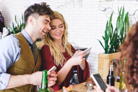 Photo pour Foyer sélectif de beau couple souriant et en utilisant des appareils numériques au café - image libre de droit