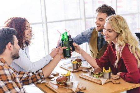 Photo pour Beaux et attrayants amis acclamant avec des bouteilles en verre et souriant au café - image libre de droit