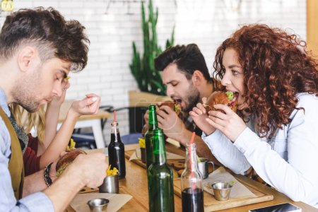Photo for Selective focus of handsome and beautiful friends eating tasty burgers at cafe - Royalty Free Image