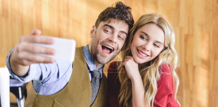 Photo for Selective focus of handsome man and beautiful woman taking selfie at cafe - Royalty Free Image