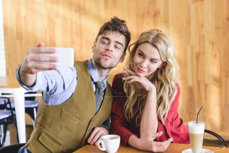 selective focus of handsome man and attractive woman taking selfie at cafe