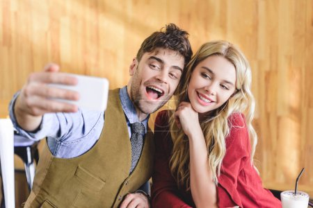 Photo for Selective focus of beautiful and smiling couple taking selfie with smartphone at cafe - Royalty Free Image