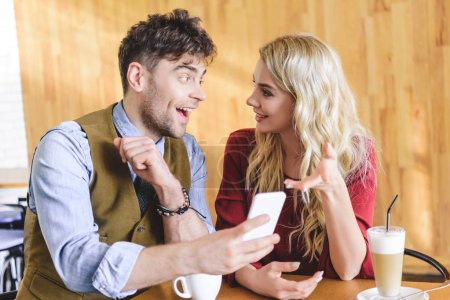 Photo pour Bel homme et belle femme à l'aide de smartphone et de parler au café - image libre de droit