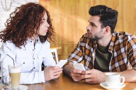 Photo for Handsome man and beautiful woman using smartphones and talking - Royalty Free Image